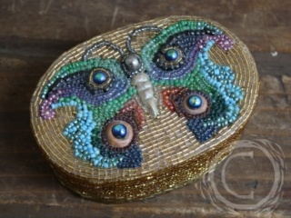 This bead mosaic box has a fanciful pattern of a butterfly on top, two tone on tone butterflies on the golden sides, and one small one on the inside.