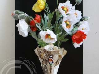 This deer skull was found in Robinson Canyon. The hunter had taken the antlers, leaving the rest of the skull in the shape of a hollow vase. A bindi of glass beads and traditional henna patterns adorn the skull matching the silk poppies arranged out the top. 3D Collage