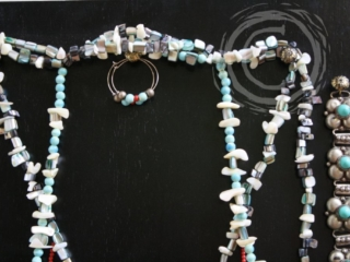 This jewelry set combines shell, turquoise, coral, and silver beads in a semi-asymmetric design to create a stunning piece of wearable art.