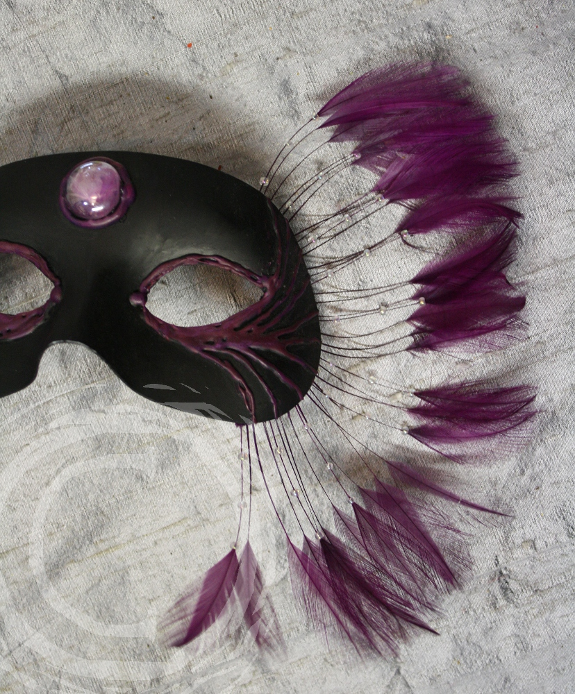 This carnival mask was created with heat reactive plastic, glass, bead work, and feathers. the central stone catches light and reflects it like a small lavender moon.