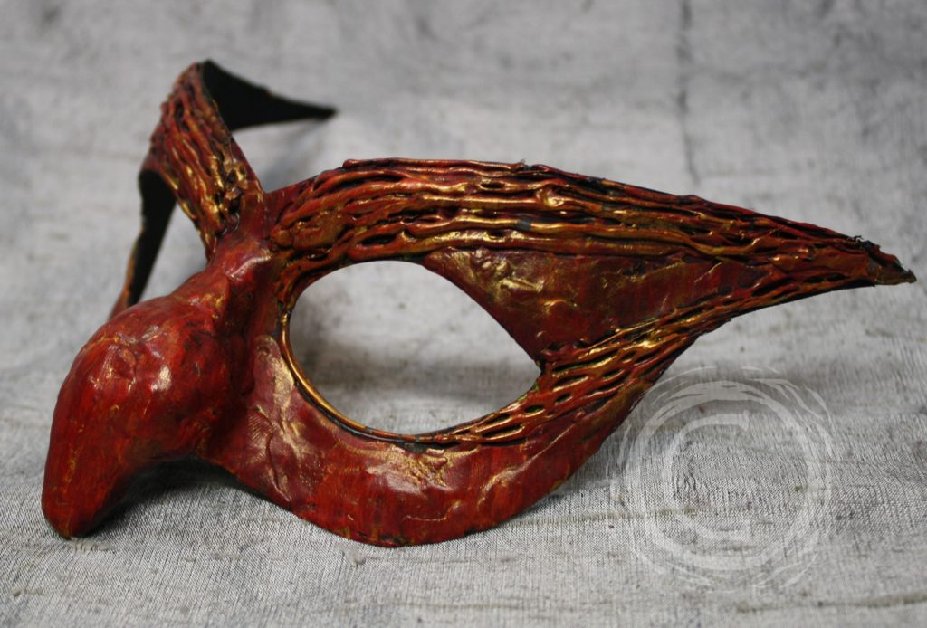 This female carnival mask has a red with gold tint coloring accenting the goblin like nose and eyebrows.
