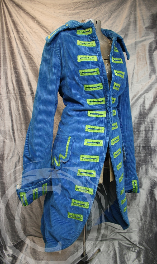 This corduroy pirate style coat has brilliant green satin accents.