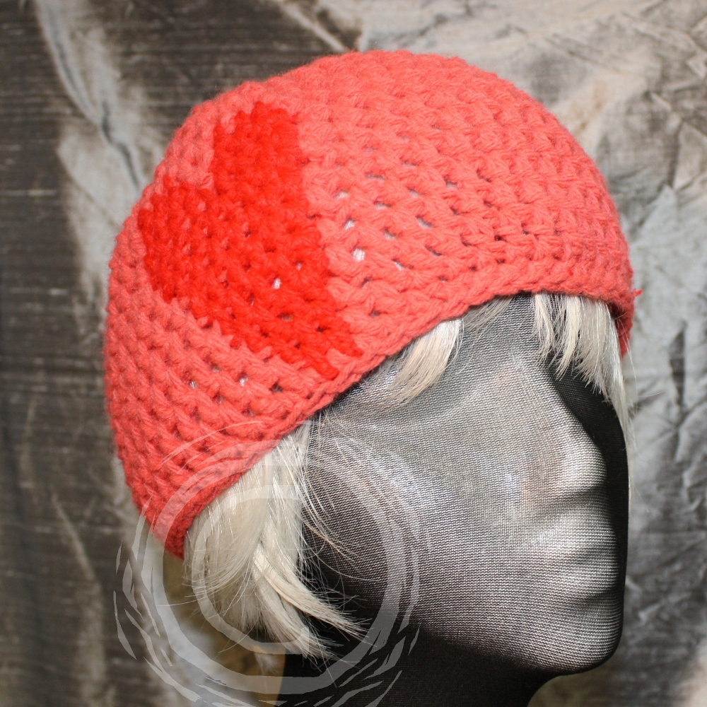 Pink crochet cloche hat with red heart design embedded in the stitch pattern.