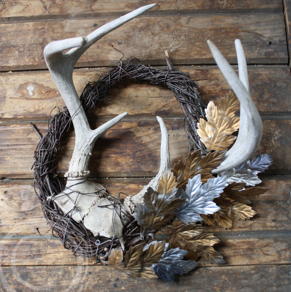 This wire and birch twig wreath holds a set of antlers accented with silver and gold silk leaves.