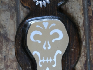 This mirror is etched with a candy skull pattern and a black rose centered on the cross above the head. Santa Muerte is an uncanonized folk saint celebrated in some parts of Central America.