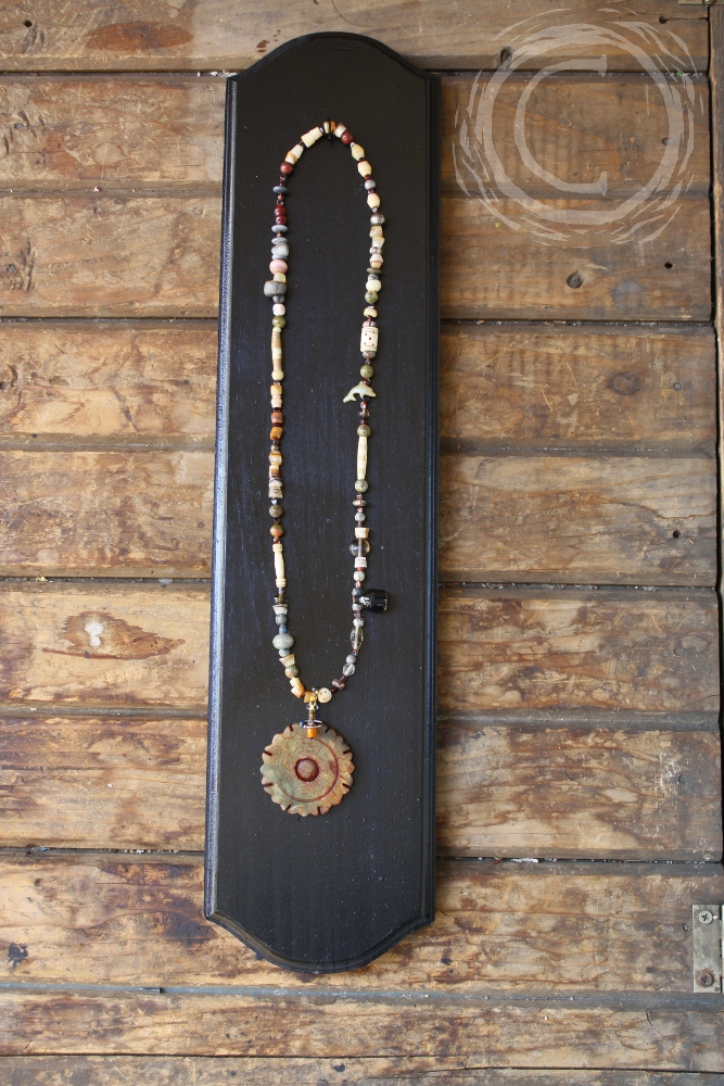 This necklace uses found objects, carved bone, stone, glass, and ceramic beads to accent a carved jasper medallion.
