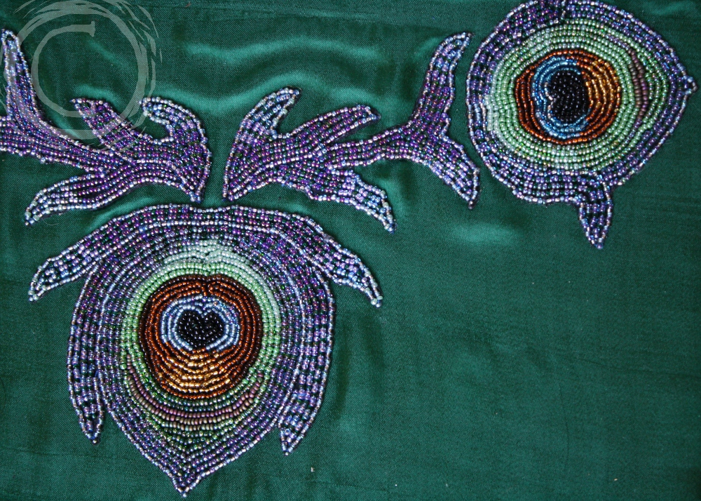 These hand beaded peacock feathers were stitched to a sheer silk and appliqued to the neckline of a formal gown. They are now remounted to a piece of vintage green silk for wall display.