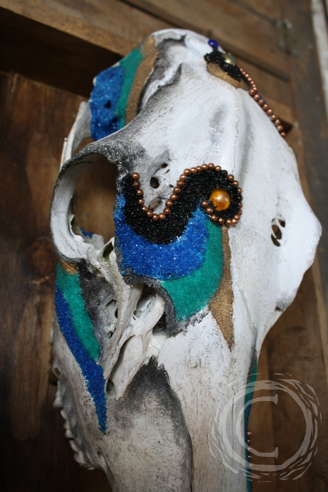 This mix media 3D collage uses colored sand, glass, and copper beads to accent the color and shape of an elk skull.