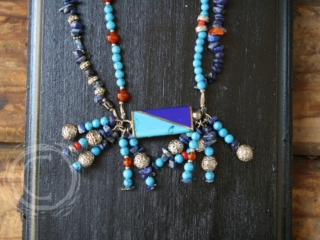 This necklace uses turquoise and lapis beads in multiple strands to accent a silver, turquoise and lapis pendant. Comes with coordinating earrings..