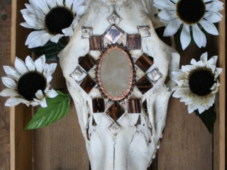 This mix media 3D collage uses white silk sunflowers, mosaic tiles, and a small oval mirror to accent the color and shape of a horse skull.