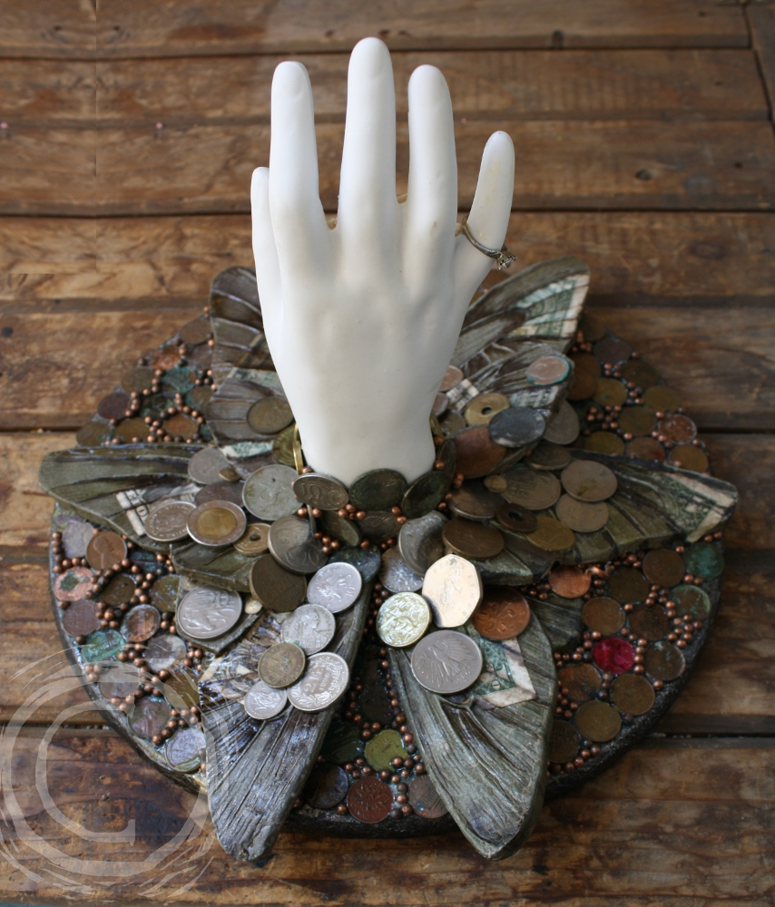 This 3D collage uses a ceramic hand, framed with resin insect wings and wearing a ring on its smallest digit, extended toward the viewer through an assortment of multinational coins, holding a collection of human and animal teeth and three natural pearls. Blue Ribbon Winner at Kittitas County Fair Fine Arts Competition.